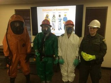 Four people in the HAZWOPER training course pose for a picture in their HAZMAT gear