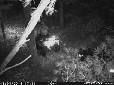 Black and white trail cam photo still of a man on an ATV with a deer strapped to the back of it.