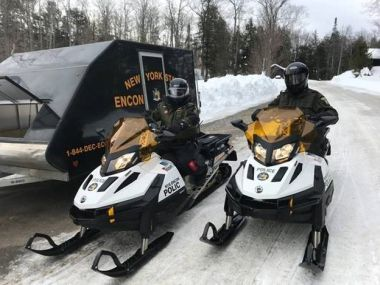 Two ECOs on snowmobiles prepare to go on Fishing Derby patrol