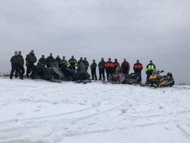 ECOs and local law enforcement pose for a picture lined up on a snowy hill with snowmobiles