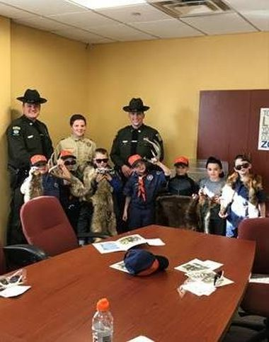 ECOs and boy scouts pose for a picture around a large wooden office table
