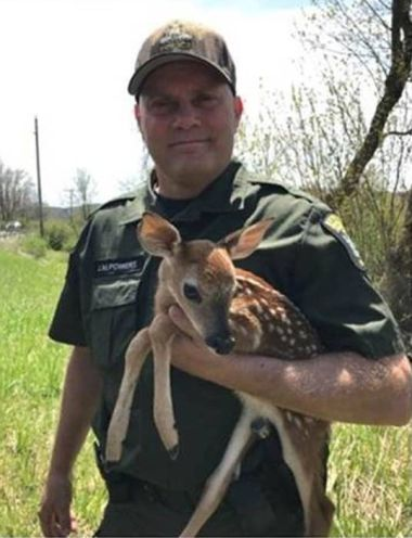 ECO holding a small fawn in his arms