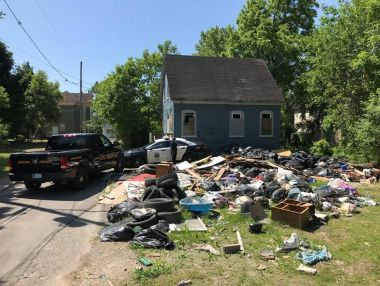 Photo of a house with a large amount of garbage and debris on the lawn outside.