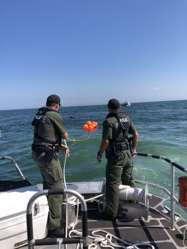 Two ECOs holding the line on a bouy on the back of a boat in the ocean