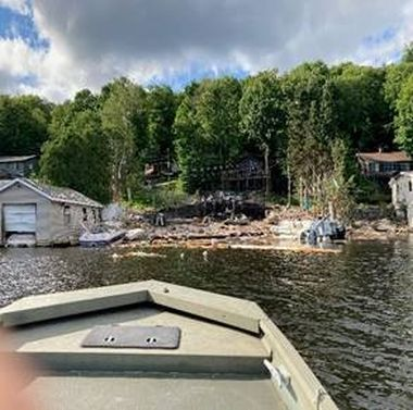 Debris along shoreline and in water from house explosion