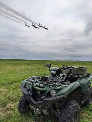 an ATV sitting in a field as the U.S. Airforce Thunderbirds fly overhead