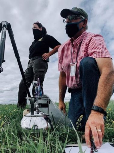 Two people in a field adjusting an air monitor