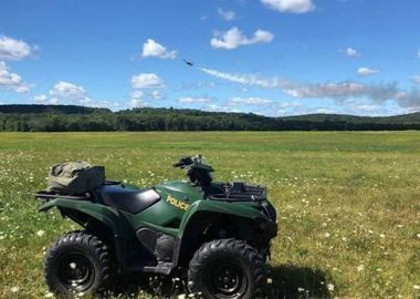 ATV in a field with mountains int he background