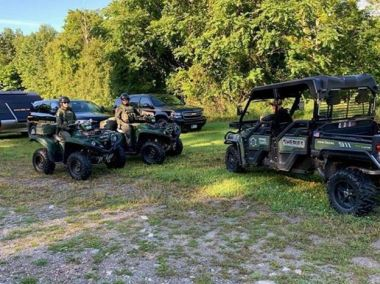 two ECOs sitting on ATVs while on patrol in the woods