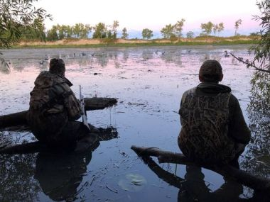 Two hunters sit at the edge of the water while waterfowl hunting