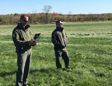 two ECOs standing in a field using a control box for a drone