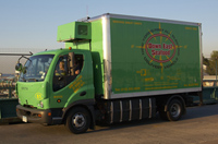 green truck with words all electric delivery vehicle on side