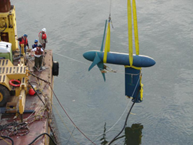 B;ie turbine being lowered into river with yellow straps from barge. Barge on left side with workers watching