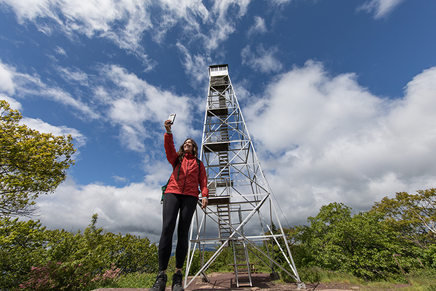 a woman taking a selfie in front of a fire tower