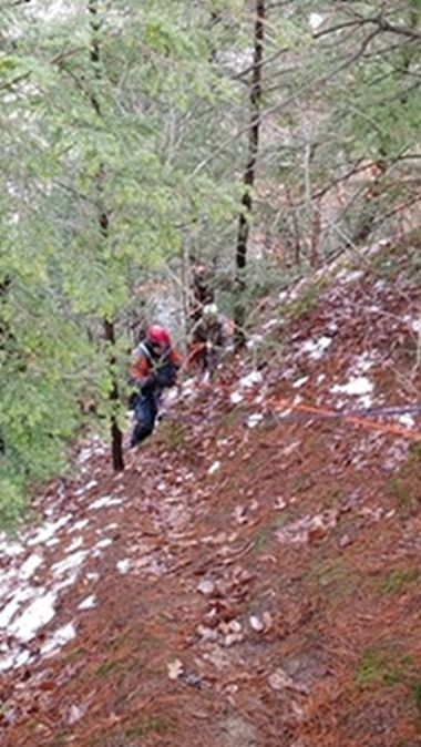 Forest Ranger climbs a steep embankment while rescuing kayaker