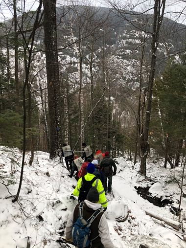 Forest Rangers hiking down a snowy mountain trail during rescue