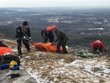 Forest Rangers and local law enforcement pull a missing man to safety over a ledge