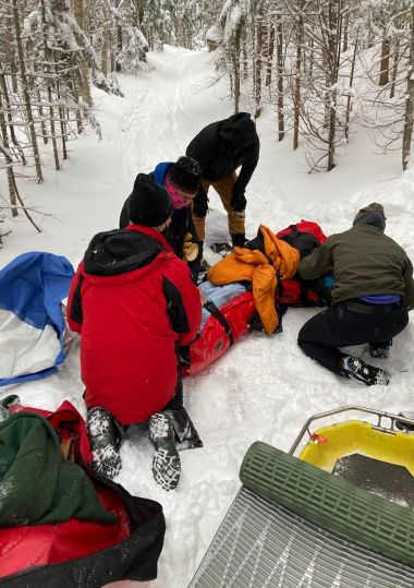 Forest Rangers wrap up injured hiker on a snowy trail