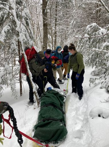 Forest Rangers carry injured hiker down a snowy trail