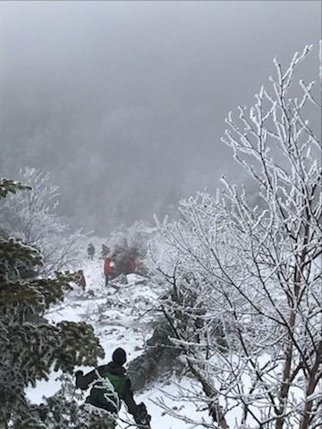 Snowy view from mountain looking down on the Forest Rangers making a rescue
