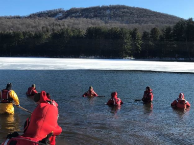 Forest Rangers chest-deep in an icy lake practicing cold water rescues