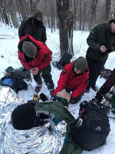 Forest Rangers tending to hikers on a snowy trail