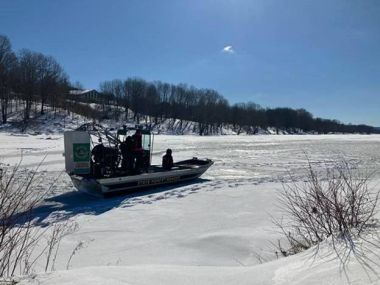 Forest Rangers on airboat moving across frozen reservoir