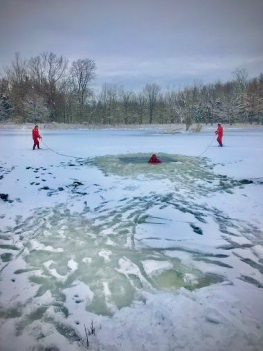 Three forest rangers practice flat ice rescue techniques