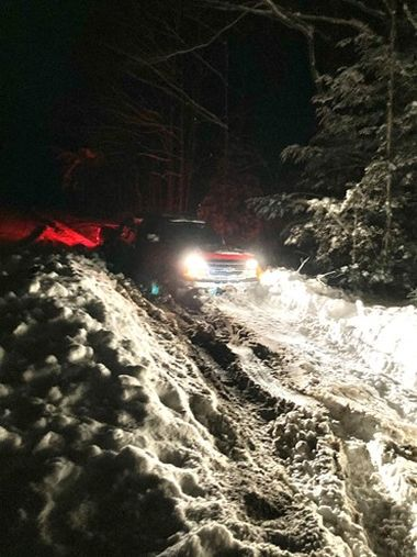 Dark nighttime photo of a truck with headlights shining on trail its stuck on