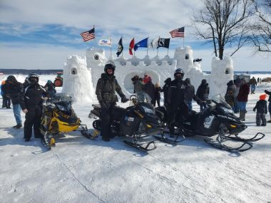 Forest Rangers and local law enforcement pose for a picture on the ice in front of a large ice castle