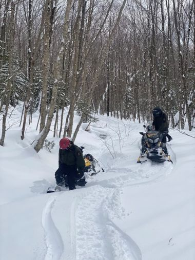 Two forest rangers on a snowmobile trail during training