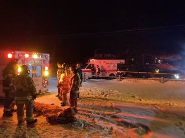 Ambulance and emergency response personnel at snowy night snowmobile accident