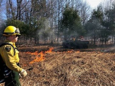 Forest Ranger stands in front of a large field monitoring the prescribed fire.