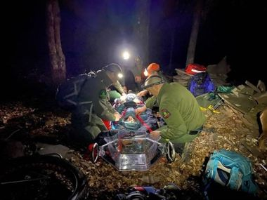 Forest Rangers with headlamps on assisting a hiker on a stretcher