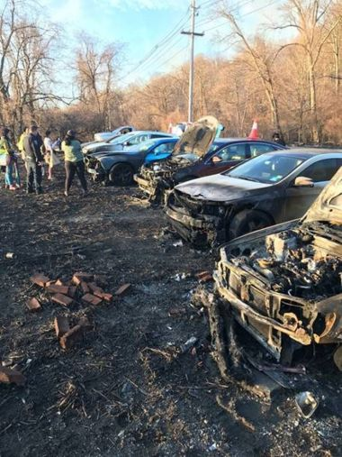 A line of cars destroyed and charred from a wildfire.