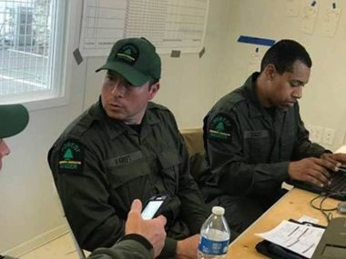 Two Forest Rangers sit at a table assisting local law enforcement and medical staff with COVID-19 response