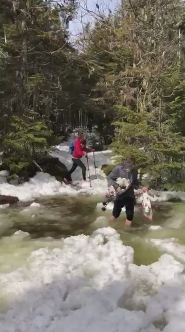 two hikers try to cross a snowy, slushy trail