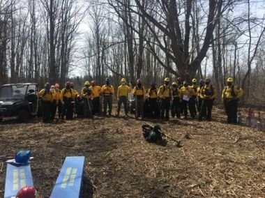 Forest Rangers and other staff line up for a photo at the edge of the woods before a prescribed burn