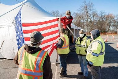 Forest Rangers stands on a table and helps hang an America Flag on the side of a white tent.