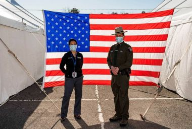 Forest Ranger stands in front of American flag at COVID-19 testing site