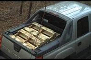 photo of a pick-up truck in the woods with wooden pallets in the back of it