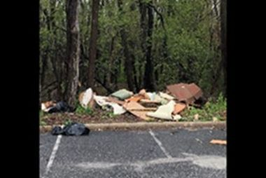 construction materials dumped at the side of the woods near a parking lot