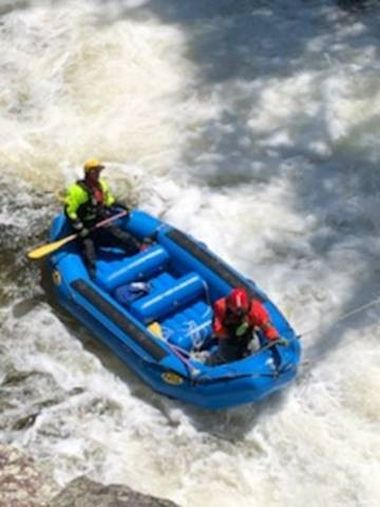 overhead view of a raft with Forest Rangers on board in an area of rushing water