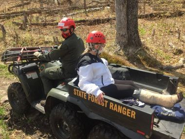 Young woman riding in the back of a Forest Ranger's UTV through the woods