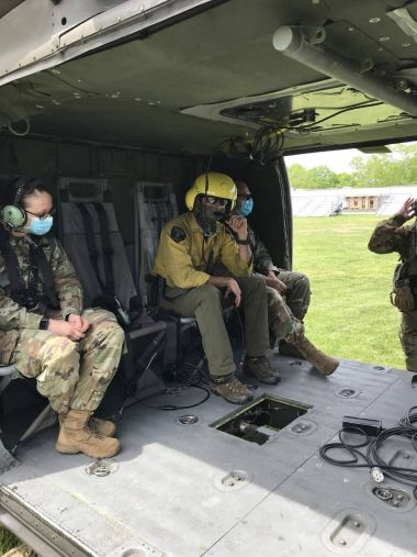 Forest rangers sitting in helicopter awaiting takeoff