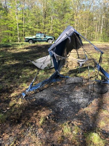 burned remains of a tent in the woods
