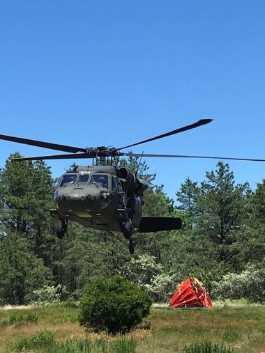A helicopter comes down for a landing in a field surrounded by trees