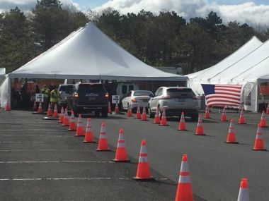 photo of a parking lot with large tents set up for COVID-19 testing
