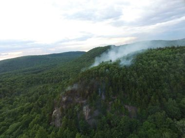 Aerial view of a wildfire smoking on a mountain