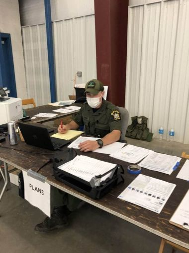Forest Ranger sits at a long wooden table while working at a COVID-19 testing site